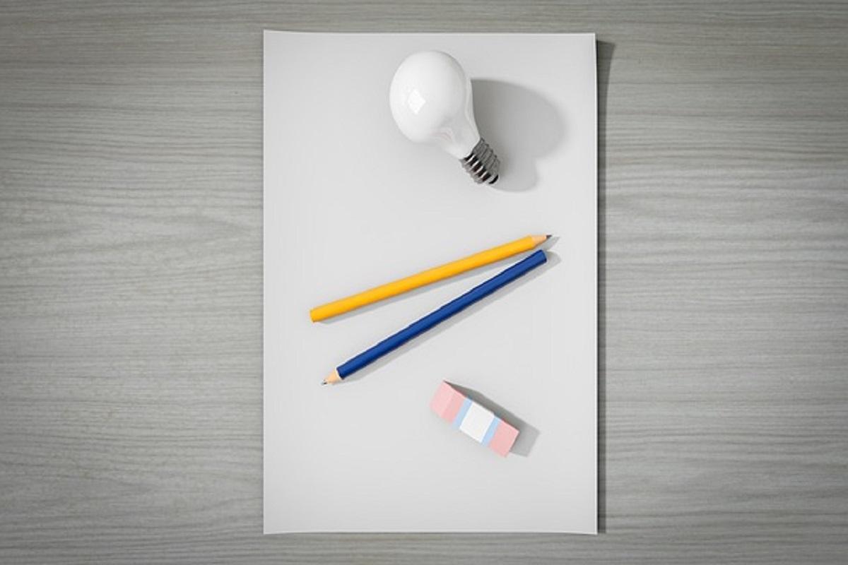 Folha em branco com lápis, borracha e uma lâmpada