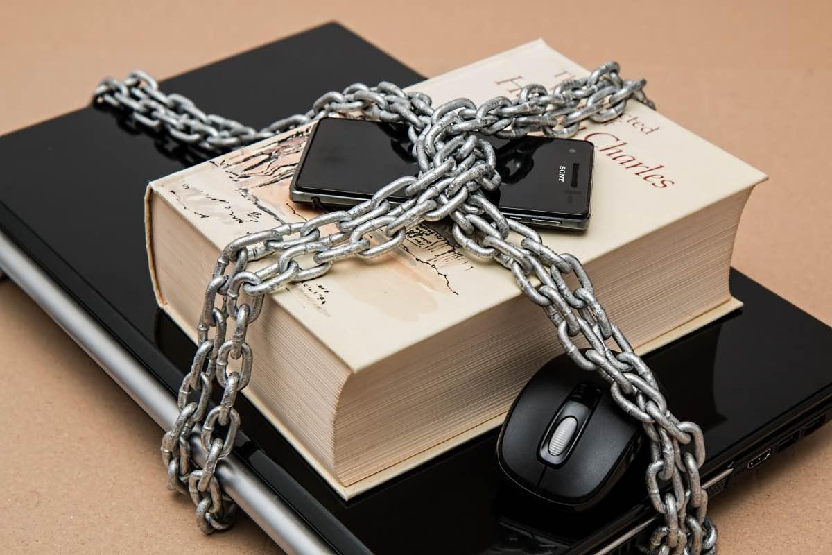 Cadeados em portátil, livro e smartphone