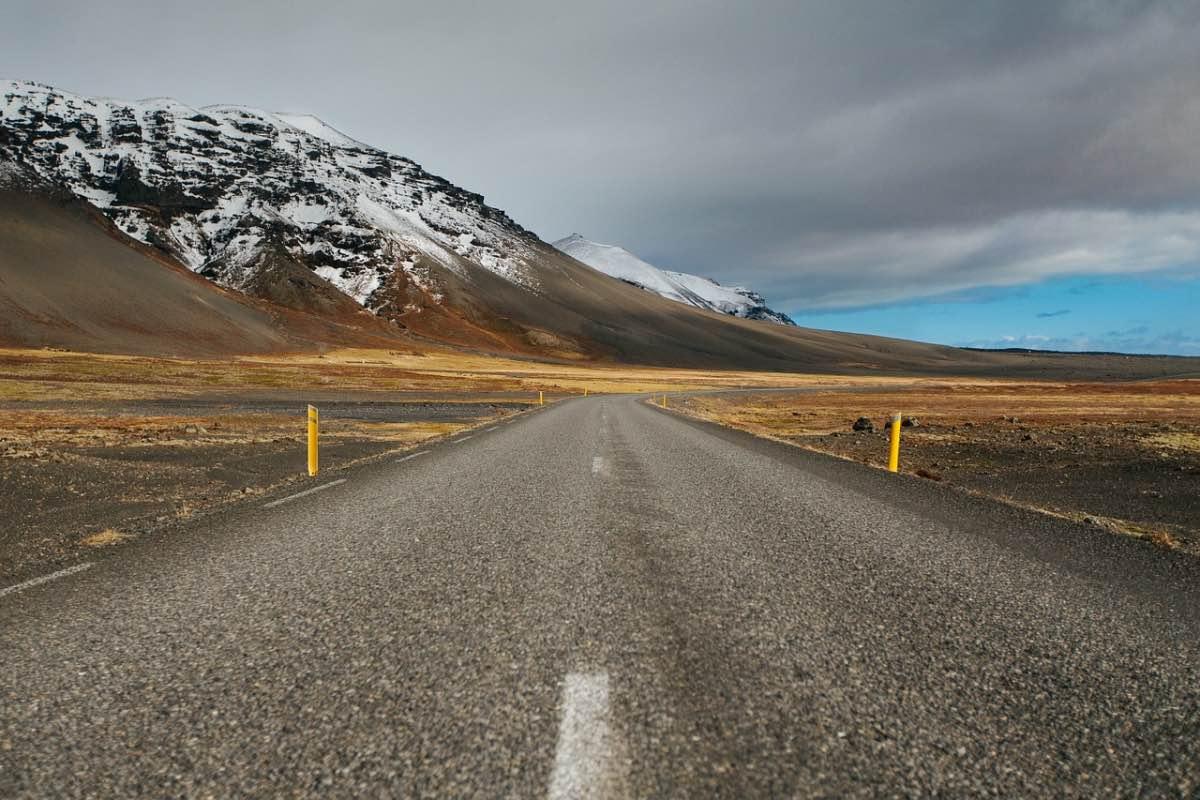 Estrada com montanhas e nuvens no céu