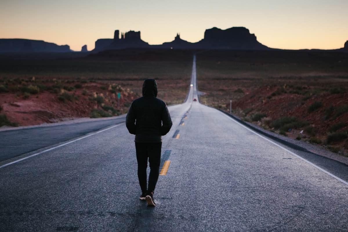 Homem a caminhar numa estrada vazia ao anoitecer