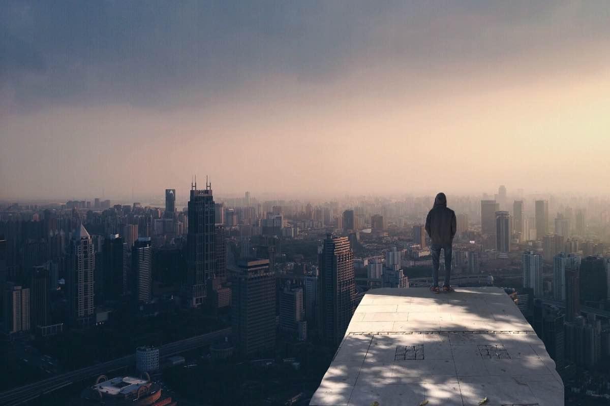 Homem a observar a vista de uma cidade
