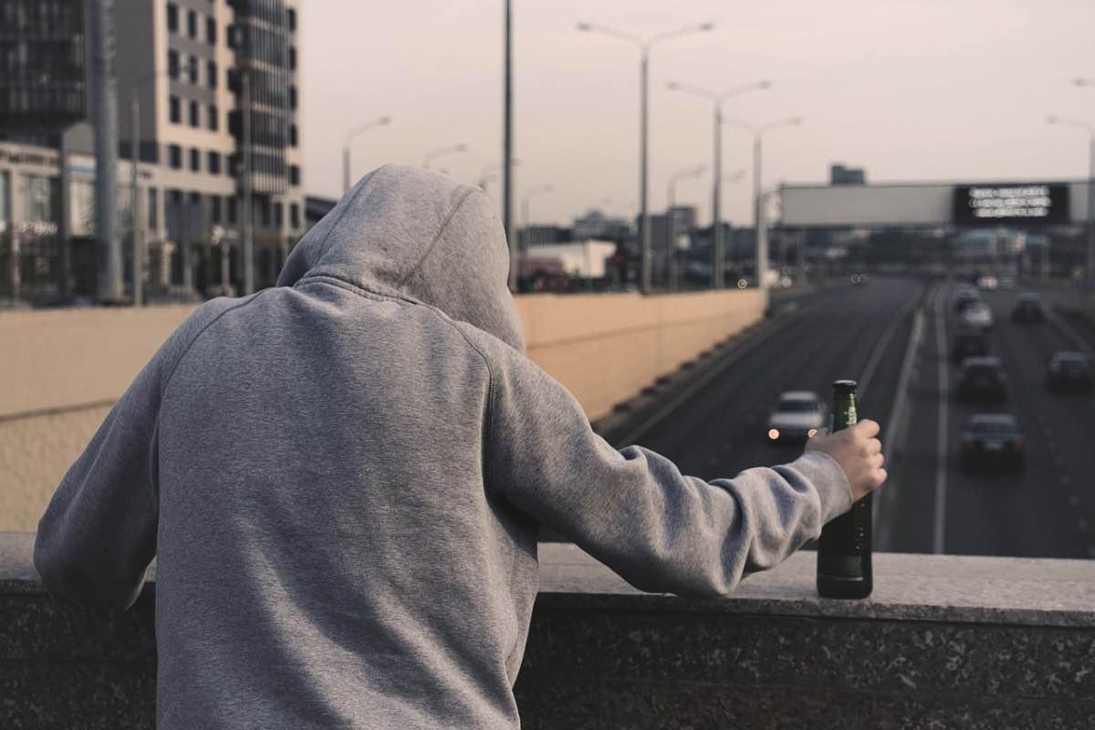 Homem numa ponte com uma cerveja