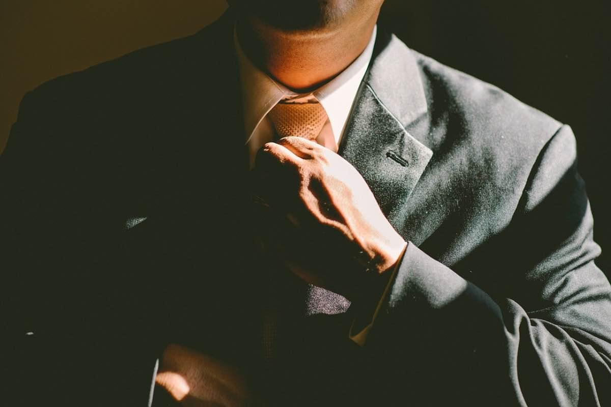 Homem de fato a ajeitar a gravata