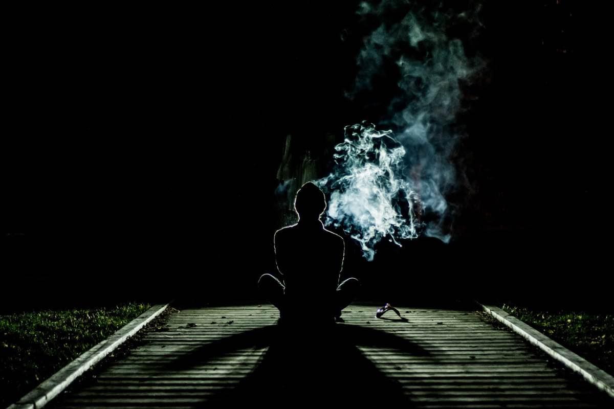 Homem sentado a fumar no escuro