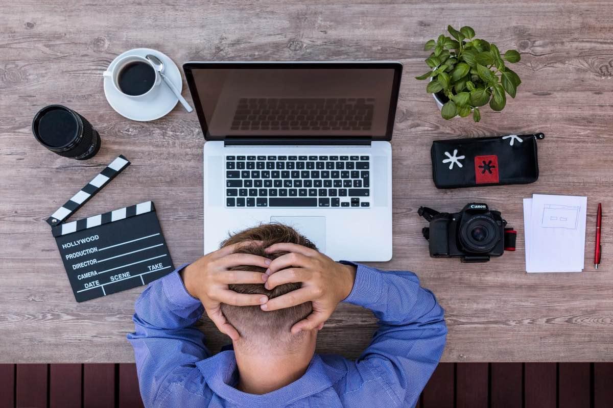 Homem à frente de um computador frustrado com as mãos na cabeça
