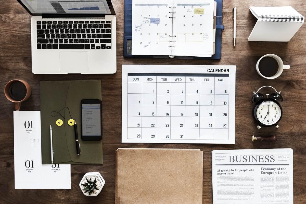 Mesa com calendário, computador. relógio e agenda