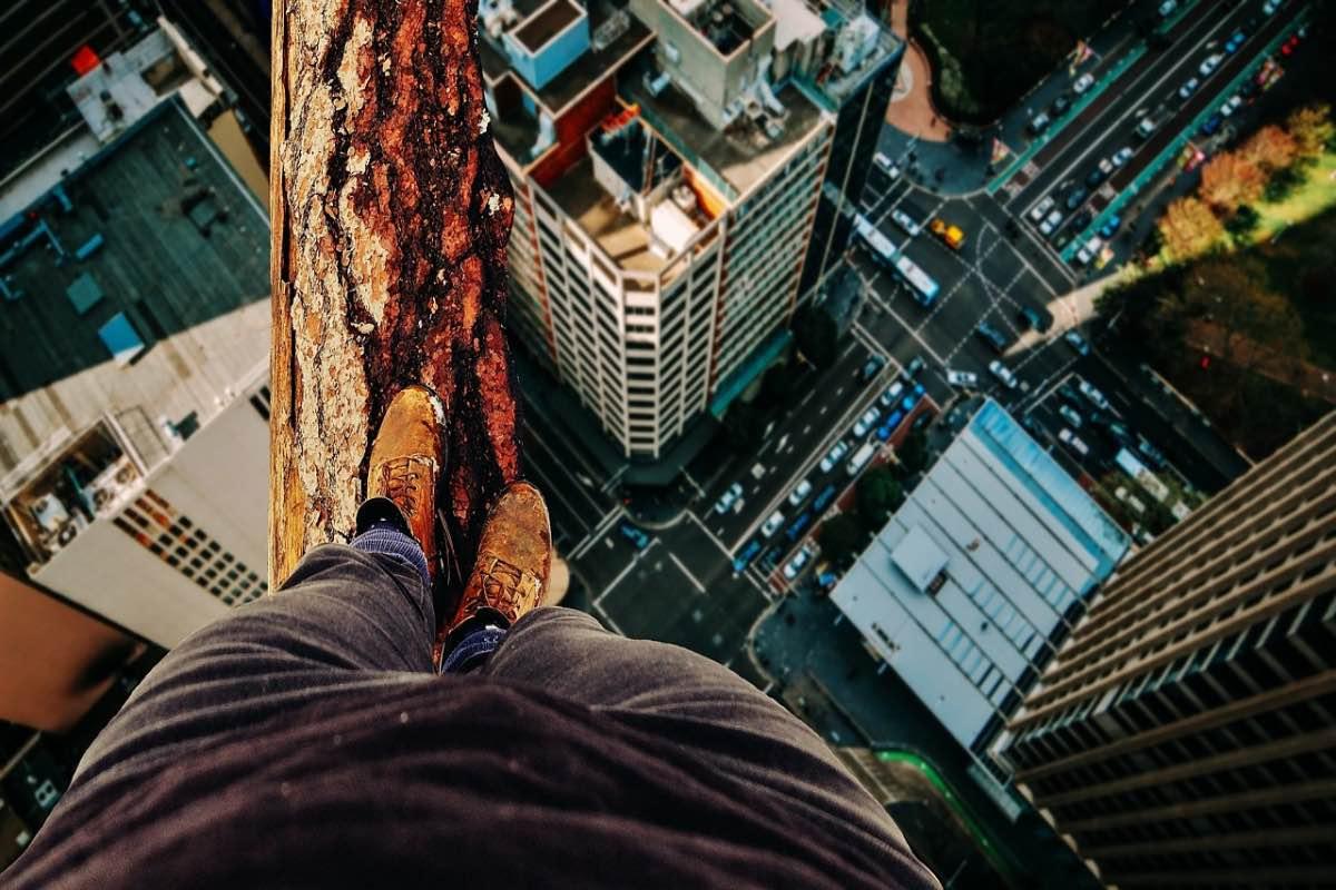 Homem em cima de um tronco numa cidade