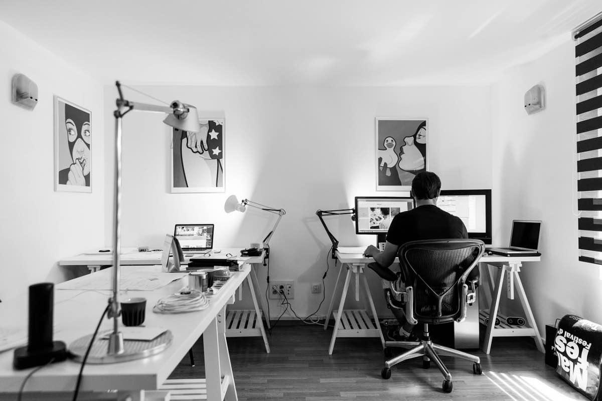 Homem sentado à frente de um computador